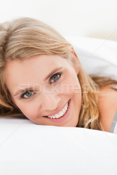 A close up shot of a woman lying in bed smiling, with her head slightly raised but still on the pill Stock photo © wavebreak_media
