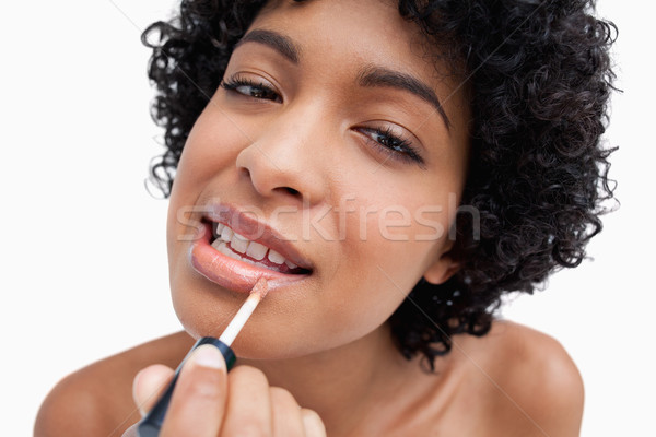 Young female applying lipstick with a lip brush in a concentrated way Stock photo © wavebreak_media
