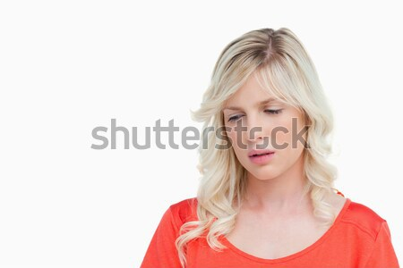 Sad woman standing upright while looking down against a white background Stock photo © wavebreak_media
