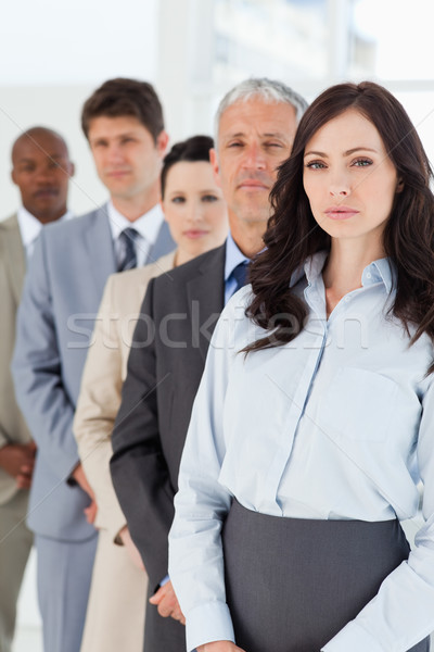 Young serious executive woman standing upright in front of her co-workers Stock photo © wavebreak_media