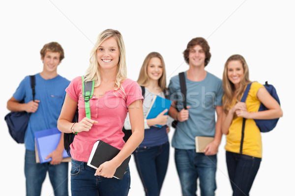 A smiling girl stands in front of her friends as she looks into the camera  Stock photo © wavebreak_media
