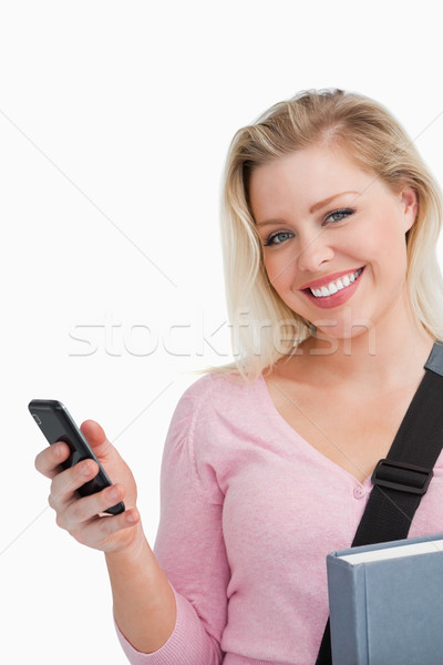 Smiling woman holding her cellphone and a novel against a white background Stock photo © wavebreak_media