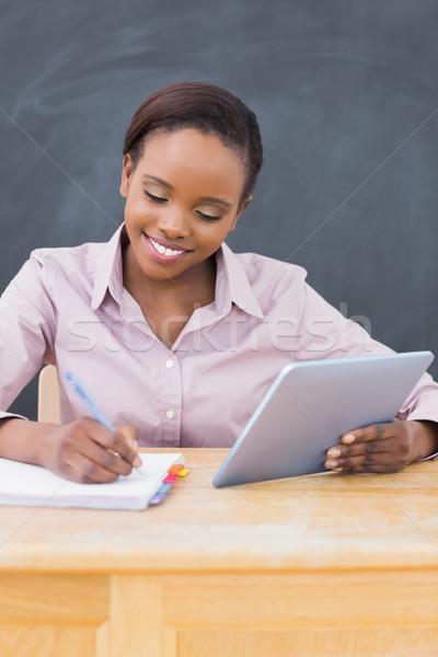 Teacher holding an ebook while writing in a classroom Stock photo © wavebreak_media