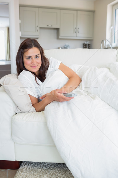 Brunette holding a remote while lying on the sofa Stock photo © wavebreak_media