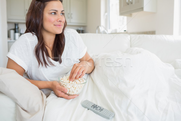 Woman watching television and eating popcorn while relaxing Stock photo © wavebreak_media