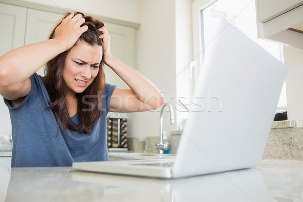 Woman getting angry while using laptop in kitchen Stock photo © wavebreak_media