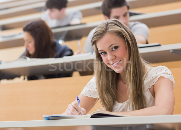 Woman sitting at the lecture hall while smiling and writing notes Stock photo © wavebreak_media