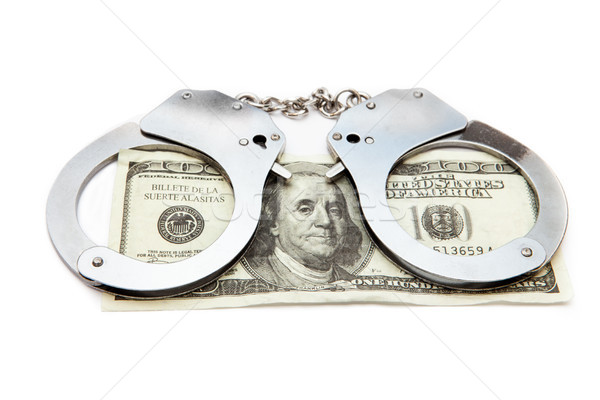 Handcuffs and money against white background Stock photo © wavebreak_media