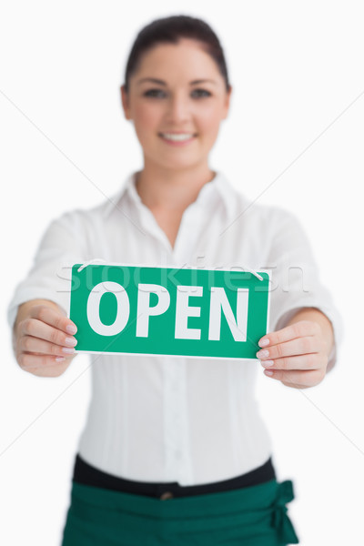 Smiling waitress holding out open sign on white background Stock photo © wavebreak_media