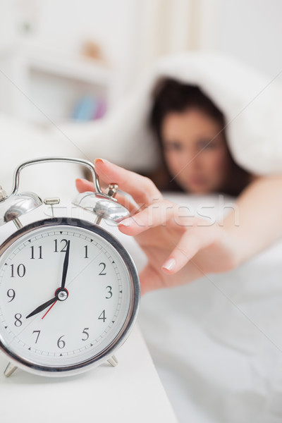 Mulher cama mão despertador casa Foto stock © wavebreak_media
