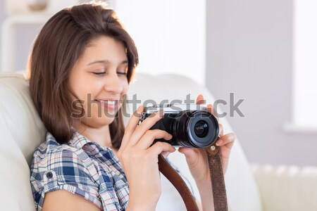 Portrait of happy young female with photographic camera Stock photo © wavebreak_media