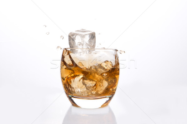 Ice cube falling in a tumbler of whiskey Stock photo © wavebreak_media