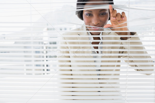 Portrait of a businesswoman peeking through blinds Stock photo © wavebreak_media