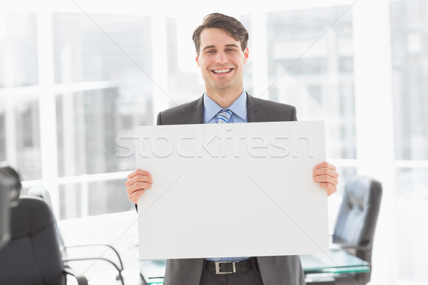 Jóképű boldog üzletember tart plakát iroda Stock fotó © wavebreak_media