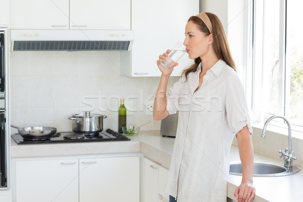 Side view of a woman drinking water in kitchen Stock photo © wavebreak_media