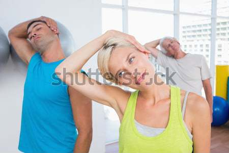Side view of determined young couple doing sit ups Stock photo © wavebreak_media