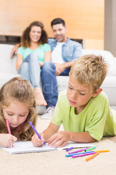 Siblings colouring on the rug with parents watching from sofa Stock photo © wavebreak_media