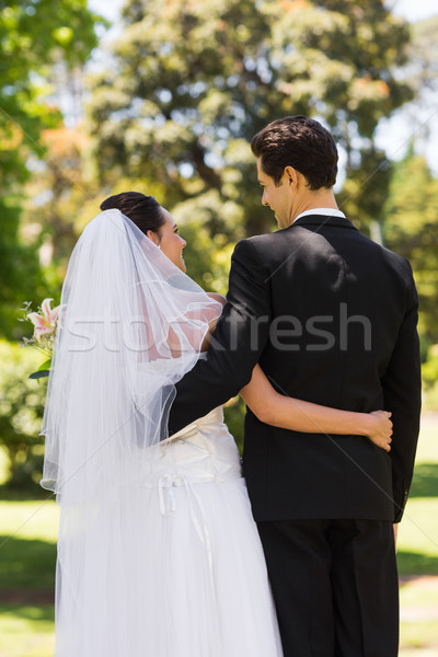 Rear view of newlywed with arms around in park Stock photo © wavebreak_media