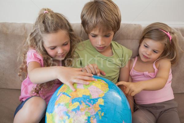 Three kids with globe sitting in living room Stock photo © wavebreak_media