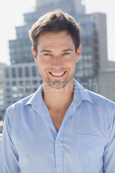 Jóképű férfi mosolyog kamera erkély napos idő ház Stock fotó © wavebreak_media