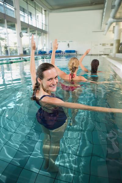 Stock photo: Female fitness class doing aqua aerobics