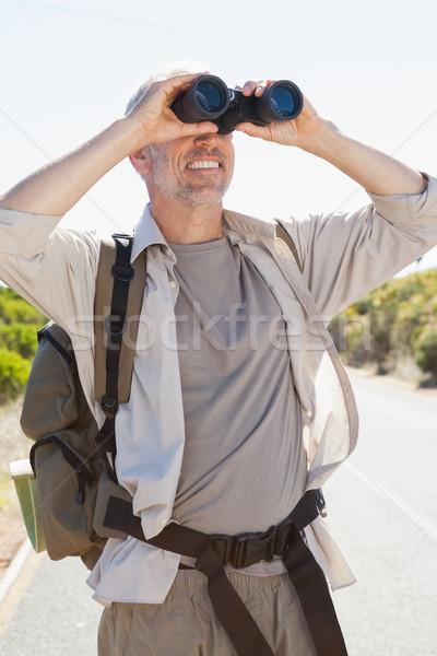Hiker standing on road looking through binoculars Stock photo © wavebreak_media