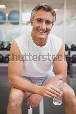Body builder holding bottles with supplements on biceps Stock photo © wavebreak_media
