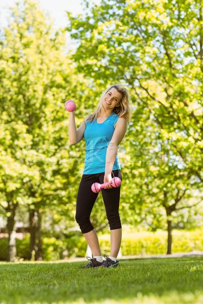 Fit blonde lifting dumbbells in the park Stock photo © wavebreak_media