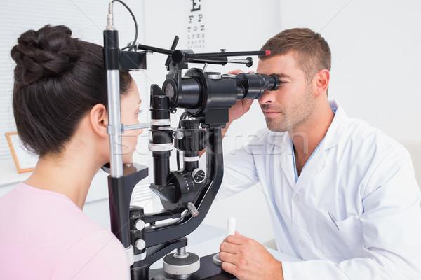 Optician examining female patients eyes through slit lamp Stock photo © wavebreak_media