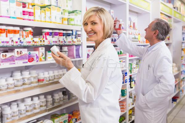 Pharmacists in lab coat looking at medicine  Stock photo © wavebreak_media