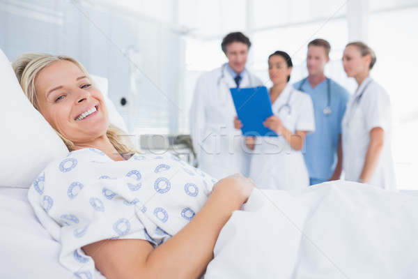 Smiling patient looking at camera with doctors behind Stock photo © wavebreak_media