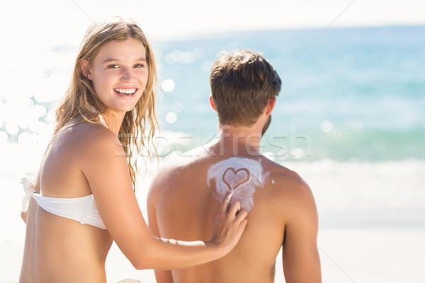 Pretty blonde putting sun tan lotion on her boyfriend Stock photo © wavebreak_media