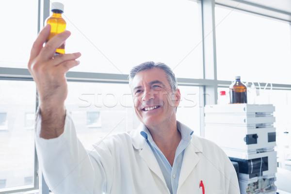 Sorridente cientista jaleco químico garrafa Foto stock © wavebreak_media