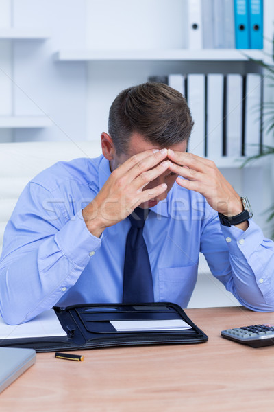 Businessman with severe headache sitting at office desk Stock photo © wavebreak_media