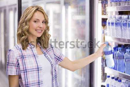 Sorridente bastante mulher loira olhando garrafa de água supermercado Foto stock © wavebreak_media