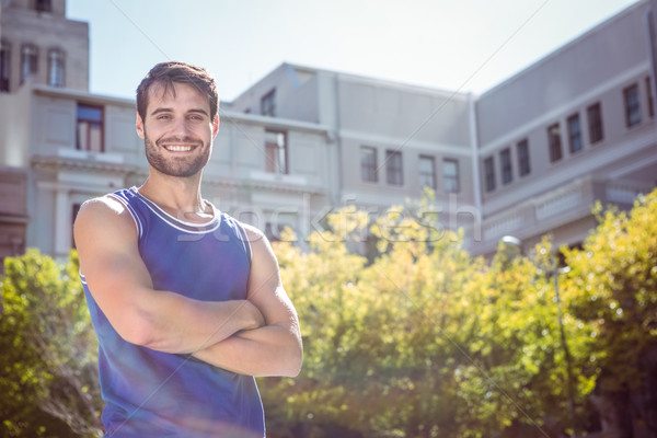 Smiling handsome athlete with arms crossed Stock photo © wavebreak_media