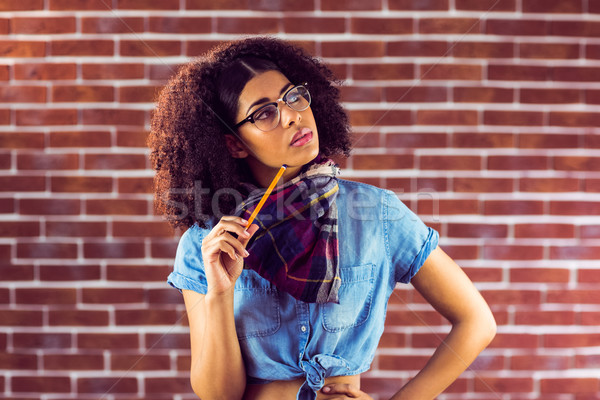 Daydreaming attractive hipster holding pen Stock photo © wavebreak_media