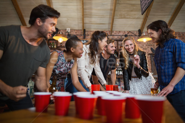 Happy friends playing beer pong game in bar Stock photo © wavebreak_media