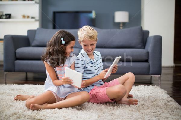 Irmãos sessão tapete digital comprimido sala de estar Foto stock © wavebreak_media