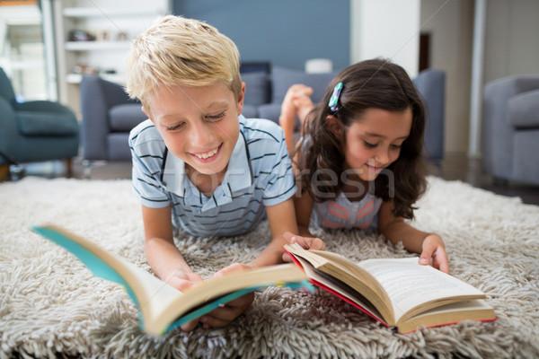 Siblings lying on rug and reading book in living room Stock photo © wavebreak_media
