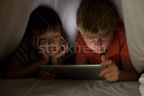 Siblings under bed sheet using digital tablet on bed Stock photo © wavebreak_media