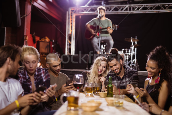 Happy friends sitting at table with musician in background Stock photo © wavebreak_media