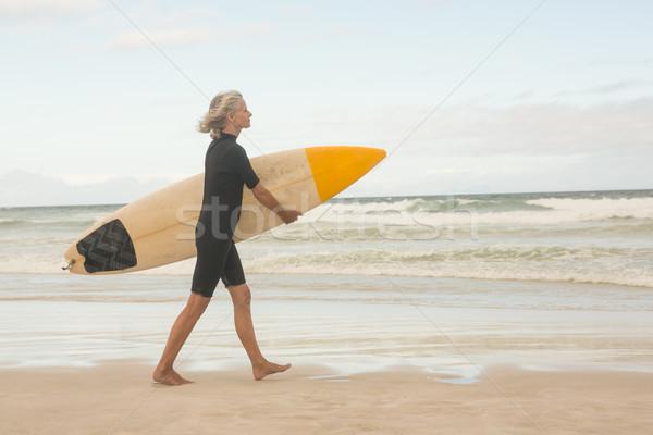 Side view of woman walking with surfboard on shore Stock photo © wavebreak_media