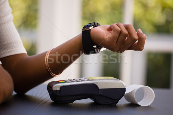 Mid section of woman making payment with smart watch and card reader  Stock photo © wavebreak_media