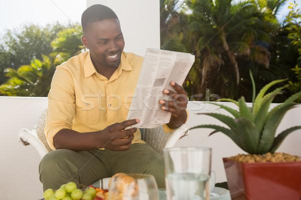 Gülen genç okuma gazete kafe oturma Stok fotoğraf © wavebreak_media