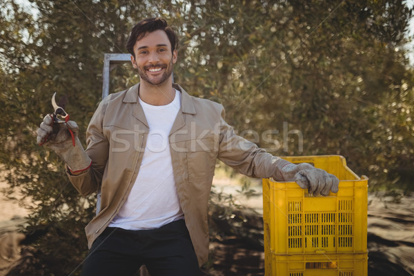 Smiling young man with pliers and crates at farm Stock photo © wavebreak_media