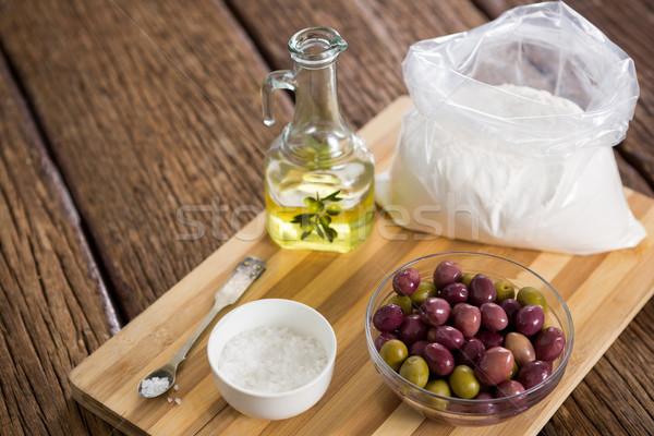 Marinated olives, oil bottle and salt on chopping board Stock photo © wavebreak_media