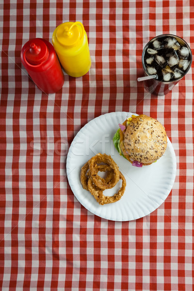 Stock photo: Hamburger, french fries, onion ring and cold drink on napkin