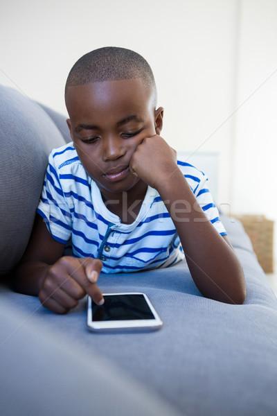 Annoiato ragazzo cellulare divano home seduta Foto d'archivio © wavebreak_media
