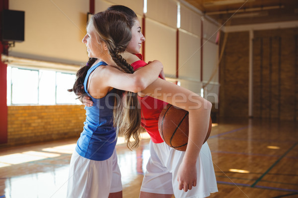 Smiling female player embracing in basketball court Stock photo © wavebreak_media
